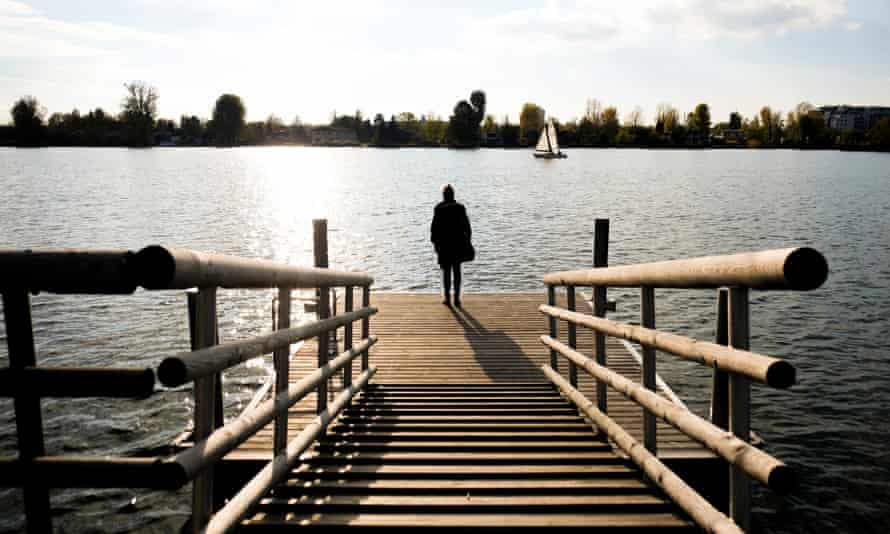 A woman standing alone on a pier.