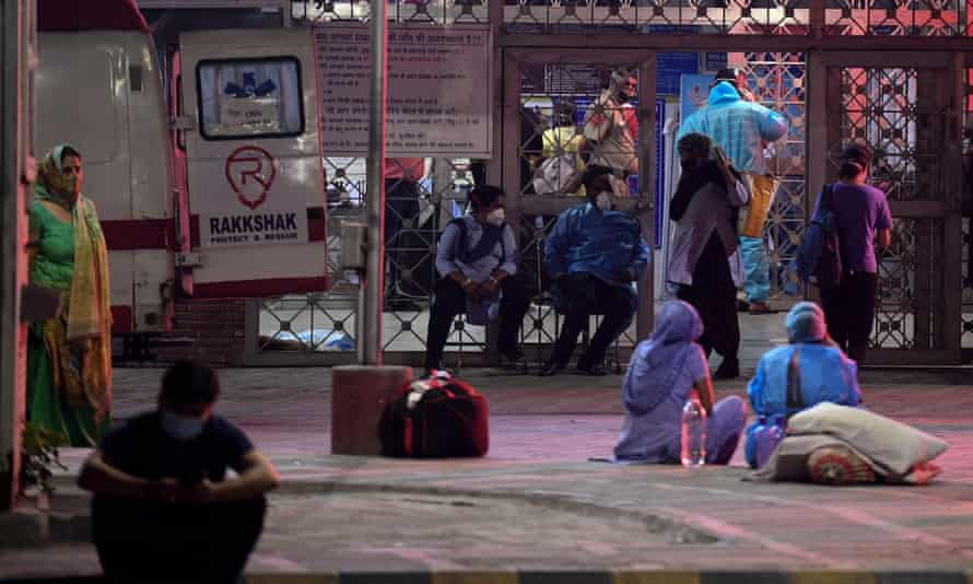 Relatives of Covid patients wait outside a hospital in Delhi