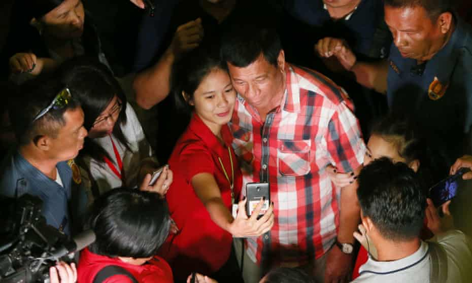 Rodrigo Duterte poses for a selfie with a supporter in his hometown in Davao city.