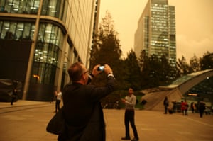 A man photographs the unusual effect among the buildings of Canary Wharf.
