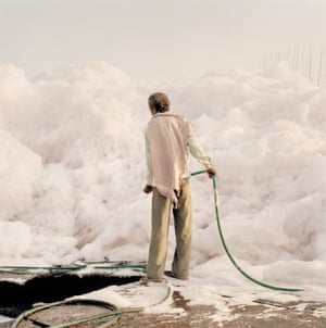 A worker with a water hose tries to tame an iceberg of foam created by the chemical waste dumped by the factories along the Yamuna river, Delhi, 2015