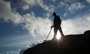 Man with metal detector silhouetted against  blue sky