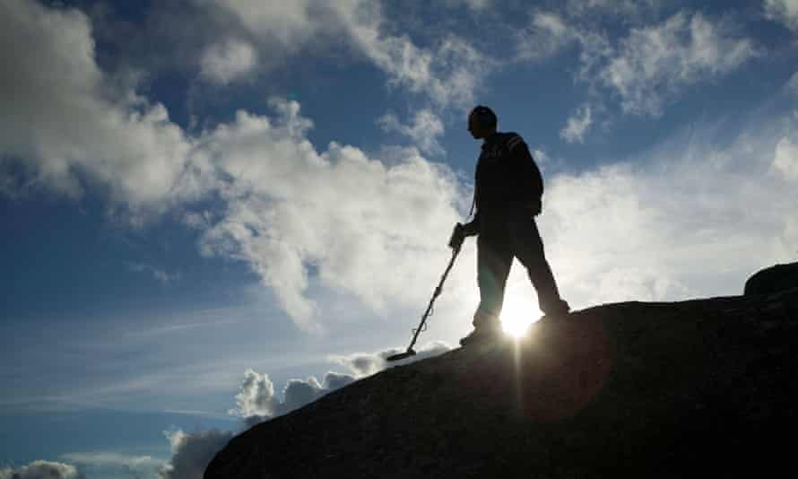 Man with metal detector silhouetted against cloudy blue sky.
