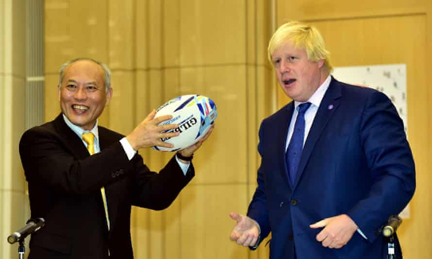 Masuzoe receives a rugby ball from Johnson