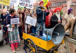 Students along with their parents hold placards and shout slogans in support of farmers protesting against the central government's recent agricultural reforms, in Amritsar, Punjab.