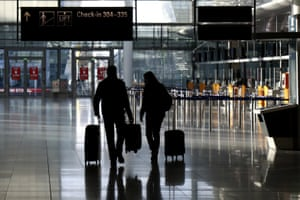 People walk through a deserted check-in hall at the airport in Munich