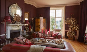 Alice Temperley's sitting room with dark red walls and sofa and ornamental touches