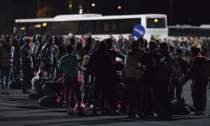 Migrants queue for buses after they arrived at the border between Austria and Hungary near Heiligenkreuz.