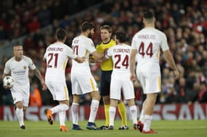 The Roma players remonstrate as referee Felix Brych shows a yellow card to Federico Fazio.