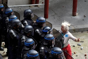 A woman stands in front of police officers as they block access to a street during a protest against proposed labour reforms in Paris on 14 June, 2016.