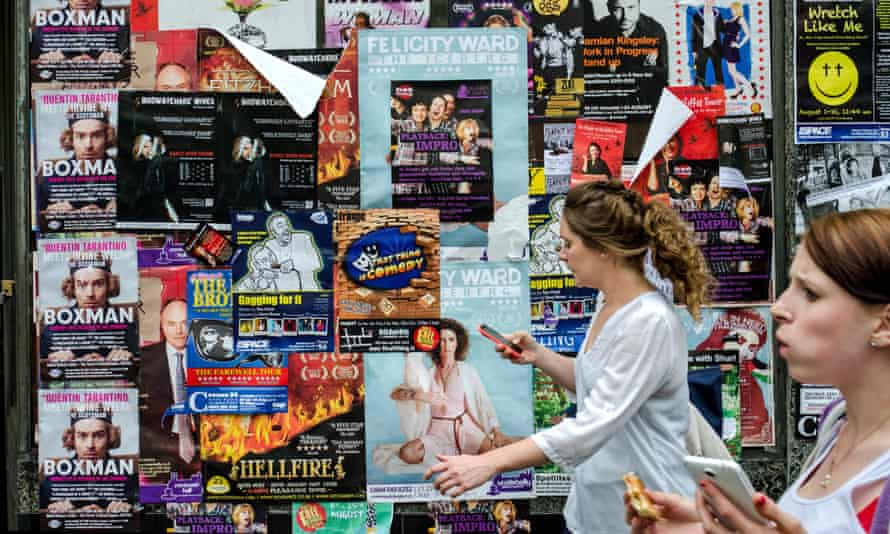 Two women walk past a wall covered in posters for fringe shows.