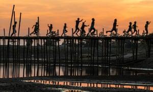 wooden bridge in Majuli with running people