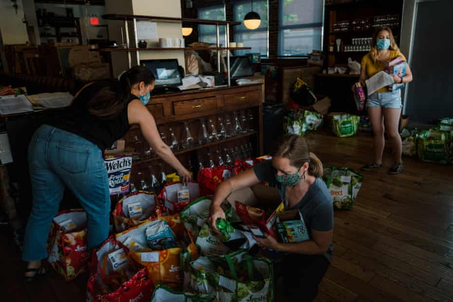 Volunteers for the Covid Care Neighborhood Network pack food into bags at the Queensboro restaurant in Jackson Heights last summer.