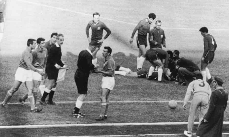 English referee Ken Aston sends off Italian player Mario David, while an injured Chilean player lies on the ground, during the 1962 World Cup meeting.