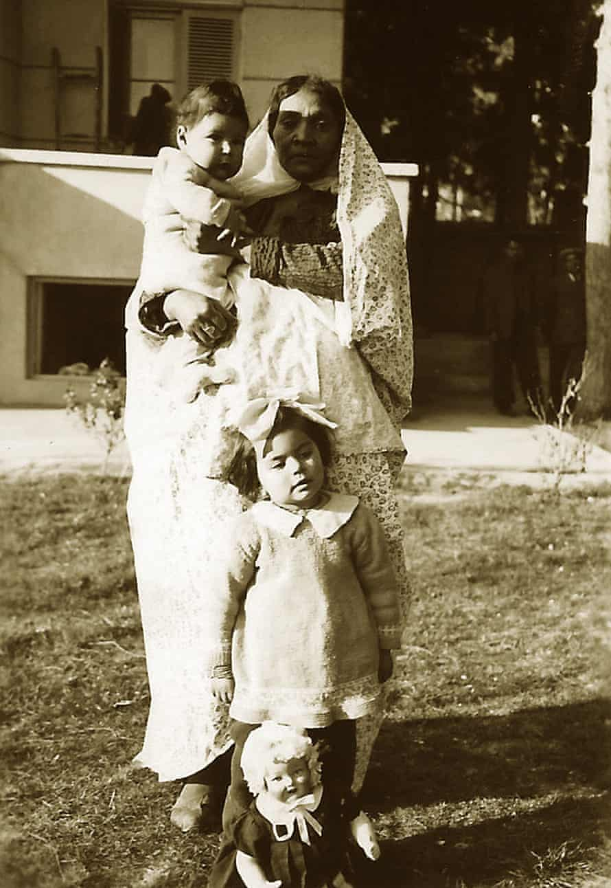 Kamran Afshar in the arms of his nanny, Naneh Sonbol Baji, and Haleh Afshar, standing behind a doll, in Tehran, 1940s. Sonbol Baji, who was of African extraction, was born in a harem and freed in childhood from the court of the last Qajar king, Ahmad Shah (1898-1930). She moved to the home of her future host family, the Afshars, where she grew up, married, and raised her son. She remained there until the end of her life.