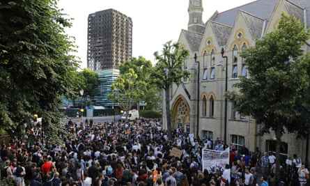 The shell of Grenfell Tower looms over protesters gathered at Notting Hill Methodist church after marching back from Kensington Town Hall.