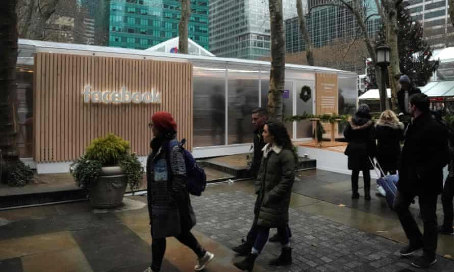 People walk by a Facebook pop-up at Bryant Park in New York City on 13 December.