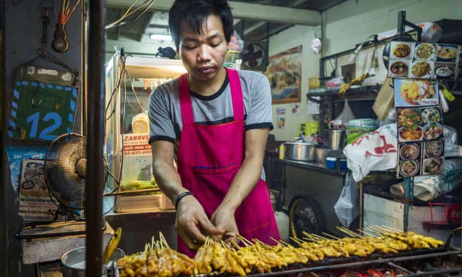 Bangkok, Thailand - A food stall vendor grills chicken ''satae Sukhumvit Road