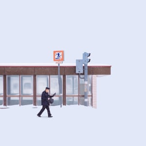 An image of a man walking past a bus stop in the snow from Chinese photographer Ying Yin's series Wind of Okhotsk
