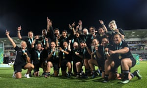 The joyous New Zealand players, sporting their winners' medals, celebrate regaining the World Cup and show off the trophy.