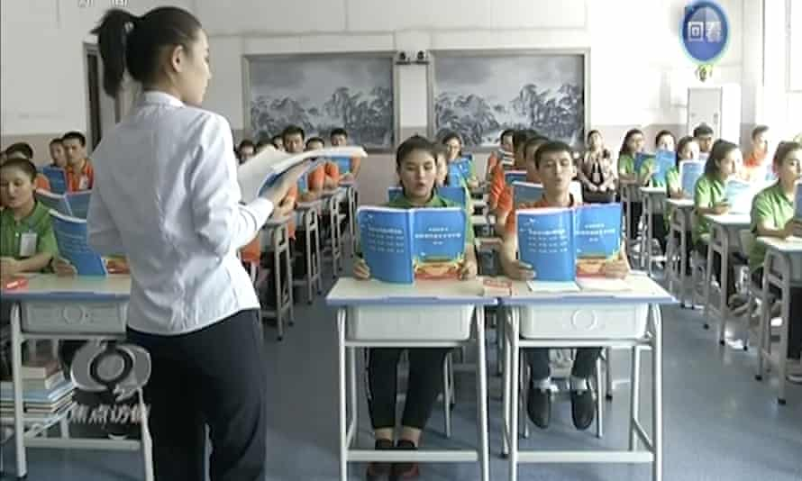 In this image from China's CCTV, young Muslims read from official Chinese language textbooks in classrooms at the 'Hotan Vocational Education and Training Center' in Xinjiang