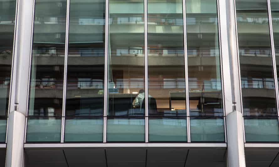 A lone worker seen through the windows of a near-empty office block in the City of London