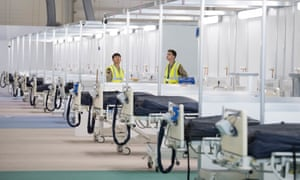 Soldiers and private contractors help to prepare the ExCel centre which is being made into the temporary NHS Nightingale hospital in London.