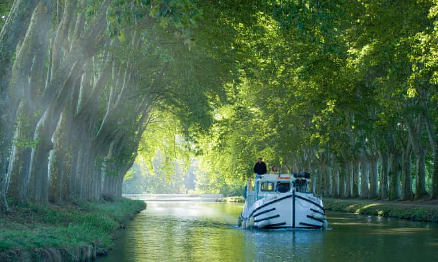 Carcassonne, boat in tree lined canal, France.