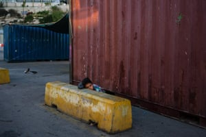 A boy wakes up at the port of Piraeus, where nearly 1,500 refugees and migrants live in a makeshift camp
