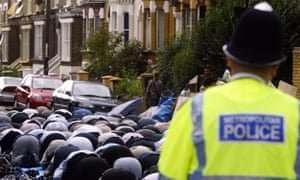 A police officer stands guard as Muslims pray outside the Finsbury Park Mosque in London