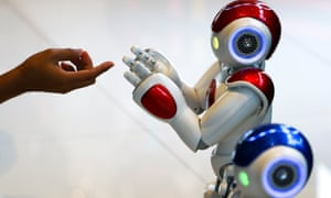 """A man plays with a """"Nao"""" humanoid robot"""