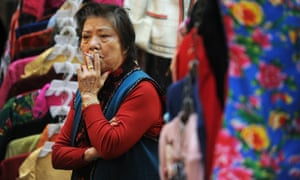 A street market vendor smokes a cigarette as she waits for customers at her clothes stall in Hong Kong.