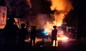 Security forces watch as a building burns after hundreds of demonstrators marched near Papua's biggest city Jayapura on Thursday night.