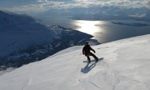 Writer Sam Haddad snowboards down the peak in the Lyngen Alps, Norway.