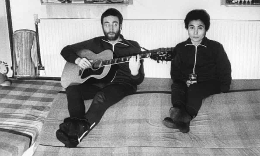 John Lennon, sitting next to his wife Yoko Ono, plays guitar in Herred during their visit to Jutland in Denmark.