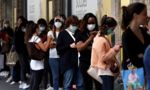 People wearing protective face masks wait before the opening of the department store Le Printemps Haussmann in Paris on the first day of summer sales.