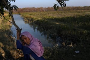 Rohingya refugee Amina Khatun, 55, rests at the bank of the Naf river after crossing it on an improvised raft to reach Bangladesh.
