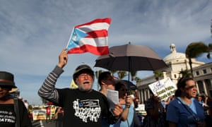 A member of a labor union shouts slogans while holding a Puerto Rico flag during a protest in San Juan September 11, 2015.