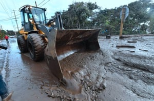 A bulldozer clears mud off the road near a flooded section of 101 freeway