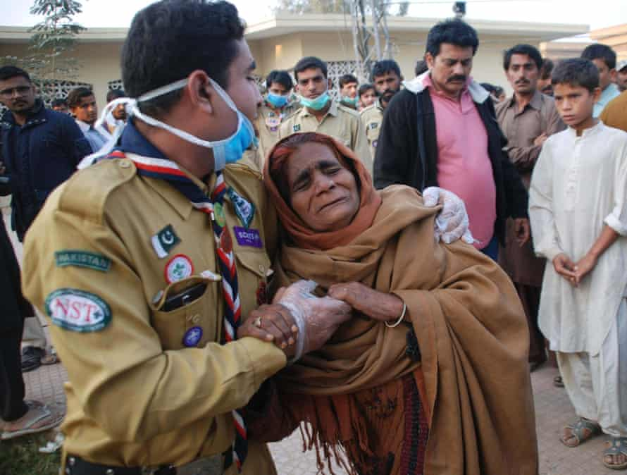 A woman whose relatives were killed in the blast is comforted near the shrine.
