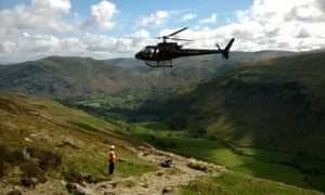 A helicopter delivers material for repair work, Ullswater Valley, Lake District.