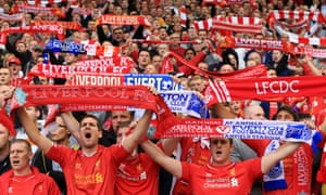 Liverpool fans hold up their scarves before a derby against Everton.