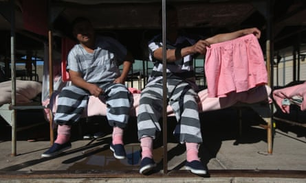 Immigrant inmates show a pair of pink underwear. The striped uniforms and pink undergarments are standard issue at the facility.