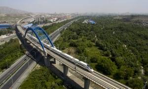 A high-speed train runs through the city of Urumqi, China.