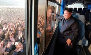 This picture released from North Korea's official Korean Central News Agency (KCNA) on October 8, 2015 shows North Korean leader Kim Jong-Un (R) waving to a crowd from a bus while inspecting a newly-built village at Paekhak-dong in Sonbong District of flood-hit Rason City.