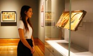 A woman views Pietro Lorenzetti's Christ Between Saint Paul and Saint Peter