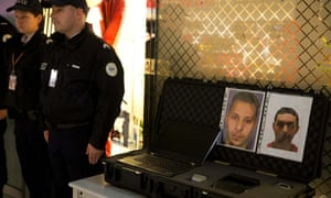 Police officers stand next to photos of Salah Abdeslam (L) and Mohamed Abrini, at Charles de Gaulle airport in France.