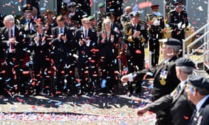 Theresa May (C), her husband Philip (4L) and defence secretary Gavin Williamson (3L) applaud as veterans and serving personnel march past.