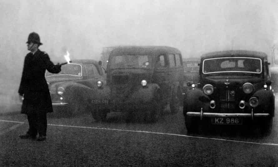 Policeman on point duty in 1952 using flares to guide the traffic during a London peasouper.