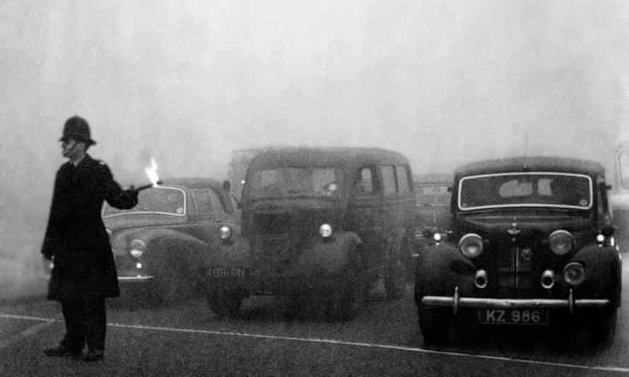 A policeman guides traffic in heavy smog in London, December 1952.